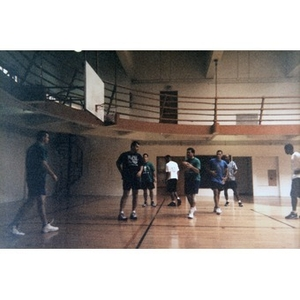 Young men playing basketball in a gym.