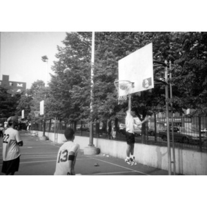 Young men playing basketball in a Villa Victoria neighborhood park.