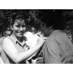 Woman pinning something on the collar of another woman.