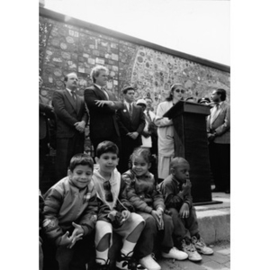 Children sitting on the curb below the speakers during Representative Kennedy's Villa Victoria visit.