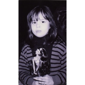 Portrait of a little girl holding a Barbie doll.