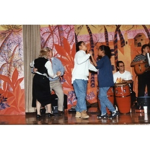 Students and teachers dancing on stage during a music and dance program organized by Inquilinos Boricuas en Acción's Areyto program.