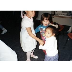 Three young children dancing together in a circle.