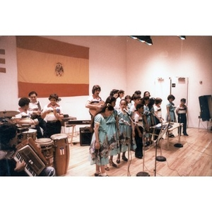 Children singing, accompanied by other children and adults playing traditional Puerto Rican musical instruments.