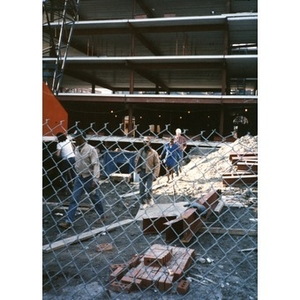 Construction workers and a female guest crossing through the Taino Tower construction site.