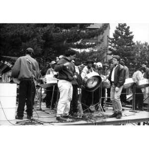 Alex Alvear (right, front) on an outdoor stage with a youth steel drum band.
