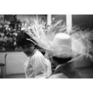 Girl looks at a boy wearing a sombrero during a performance.
