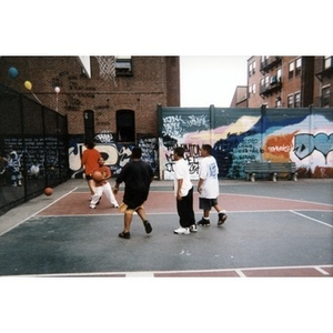 Young boys playing basketball on a court in the Villa Victoria neighborhood.