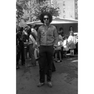 Full-length portrait of a Hispanic American man wearing sunglasses at a Latino street festival.