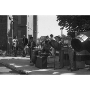Five Hispanic American boys play music at a Latino street festival, while people talk in the background.