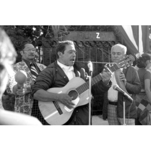 Hispanic American musician singing and playing a guitar at a Latino street festival.