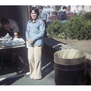 Young woman wearing a denim shirt stands next to food vending stand at a Latino street festival.