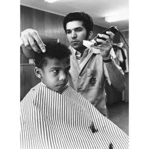 A young boy receives a haircut from a barber.