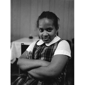 Young girl seated in dining area with arms crossed.