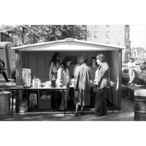 A group of six women talking at a food vending stand at a Latino street festival.