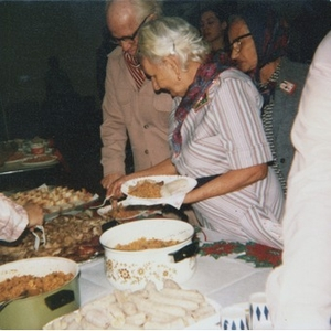 Elderly people standing in line and serving themselves food from a buffet.
