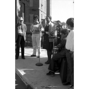 Woman speaks into microphone holding a rolled sheet of paper at a Latino street festival, with onlookers listening and musicians waiting to play music.