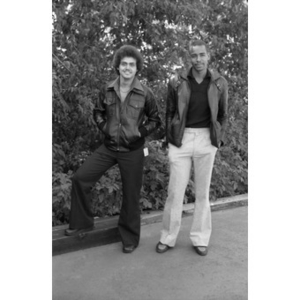 Full-length portrait of two Hispanic men wearing leather jackets, standing, facing front, at a Latino street festival.