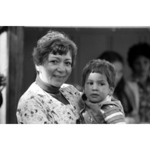 Head-and-shoulders portrait of a woman holding a little boy in her arms at a Latino festival.