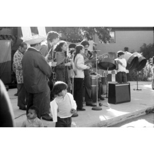 Musical group consisting of two men and two women perform at a Latino street festival, as adults and children listen and watch.
