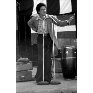Hispanic American man speaks into two microphones at a Latino festival; he is standing and gesturing to the right with his left hand outstretched.