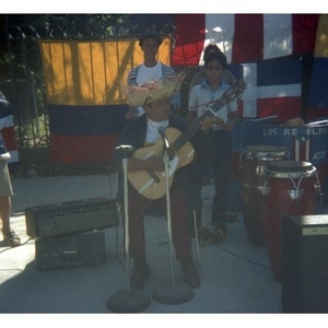 Male, Hispanic American musician wearing a sombrero plays a guitar at a Latino street festival; on the right, a boy plays maracas.