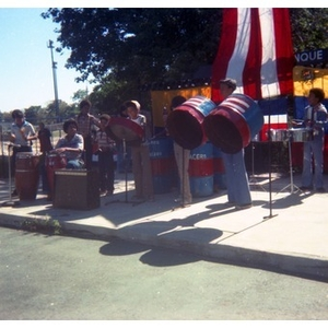 Band consisting of seven Hispanic American boys and young men play the drums at a Latino street festival.