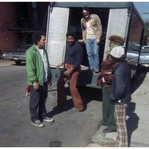 Four men and a boy stand at the rear of a truck containing items to be hauled to a Latino street festival.