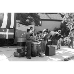 Hispanic American band, consisting of boys and young men, plays music at a Latino street festival.