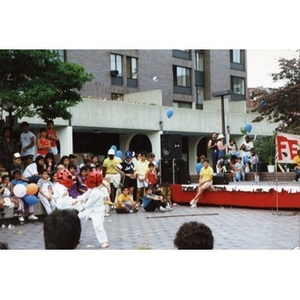 Two young Latino children give a karate demonstration while a crowd of people watches in the Plaza Betances, during the Festival Betances, 1986.