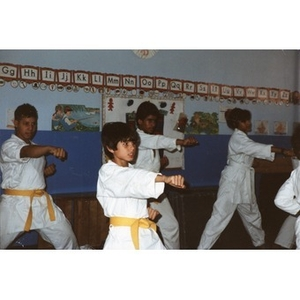 Four Latino students performing a karate demonstration in a classroom at the Festival Betances, Boston, 1986.