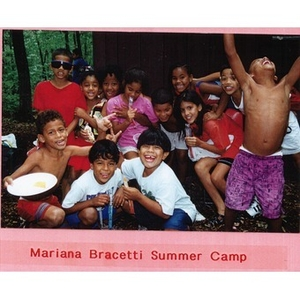 Twelve Latino children laughing, smiling at Mariana Bracetti Summer Camp; most of the children are holding candy or food in their hands.