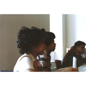 Three Hispanic American teenagers seated in a classroom, listening.