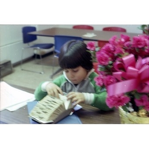 Hispanic boy seated at table looking at names and addresses in a Rolodex file at La Alianza Hispana, Boston.