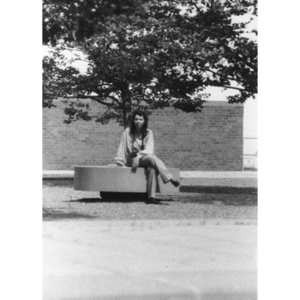 A young Hispanic women seated on a bench, outside, at a La Alianza retreat, at an unidentified campus, [Aug.?] 1978.