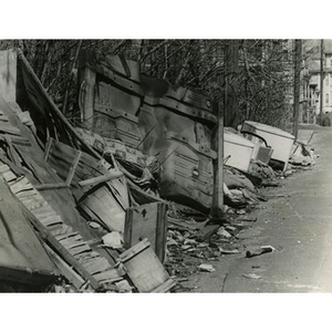 Broken crates, appliances, and rubbish piled along the side of Dacia Street, off of Quincy Street, in Roxbury, Mass.
