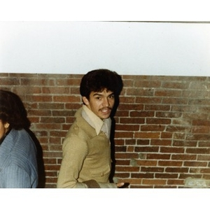 Hispanic American male employee wearing a beige sweater standing in front of a brick wall at a Christmas party at La Alianza Hispana offices, Roxbury, Mass.