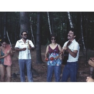 Group of four people stand in the woods playing musical instruments, singing, or clapping their hands at a La Alianza staff picnic at an unidentified location.