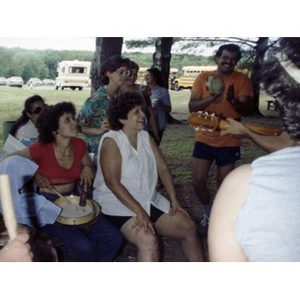 People play musical instruments while others listen and smile at a La Alianza staff picnic at an unidentified location in the woods.