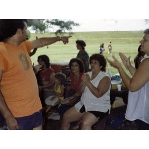 People seated and standing by a picnic table clap their hands and play musical instruments at a La Alianza staff picnic, while the man on the far left points to something in the open field behind them.
