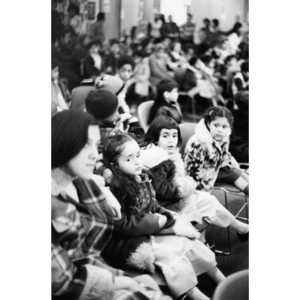 Audience watching the Three Kings' Day pageant at La Alianza Hispana, with a close-up view of a woman and three young girls seated together in a row.