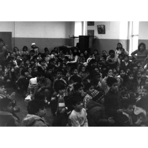 Audience, consisting mostly of Hispanic American children, seated on the floor, watches the Three Kings' Day celebration at La Alianza Hispana.