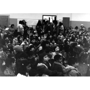 Audience, consisting mostly of Hispanic American children, seated on the floor, at a Three Kings' Day celebration at La Alianza Hispana.