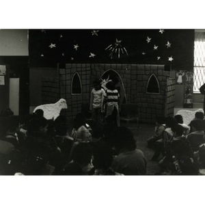 Two children perform in the Three Kings' Day celebration in front of an audience consisting mostly of Hispanic American children and some adults at La Alianza Hispana, Roxbury, Mass.