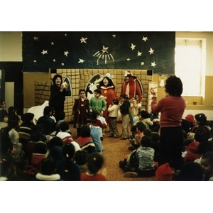 Audience watches four little girls and two clowns onstage at a Three Kings' Day celebration at La Alianza Hispana, Roxbury, Mass., while two women stand to their feet and applaud.