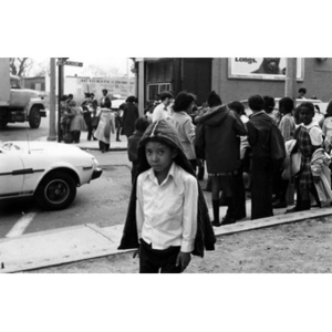 Hispanic American boy stands on the corner of Dudley Street and Mt. Pleasant Avenue, just outside of La Alianza Hispana headquarters in Roxbury, Mass., while groups of children congregate behind him.