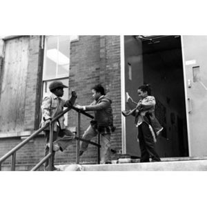 After attending a youth services program, two Hispanic American girls and one boy play on the steps outside of La Alianza Hispana headquarters, 409 Dudley Street, Roxbury, Mass.