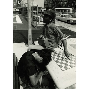 Two male Hispanic American teenagers seated at a checkerboard table at a park in Roxbury, Mass.
