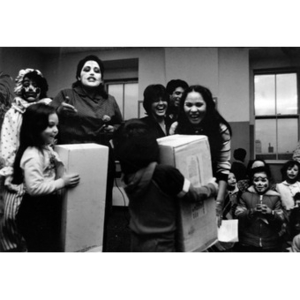 Two young girls receive prizes at a dance competition at La Alianza Hispana headquarters; two adults and some children are wearing clown makeup at this event.