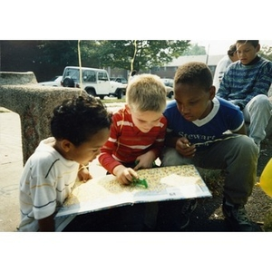 Three boys look at a picture book, seated outside.